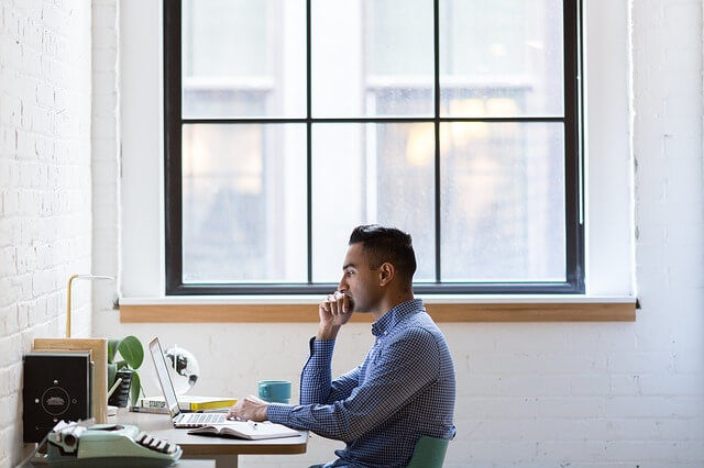 窓際でパソコンを見る男性