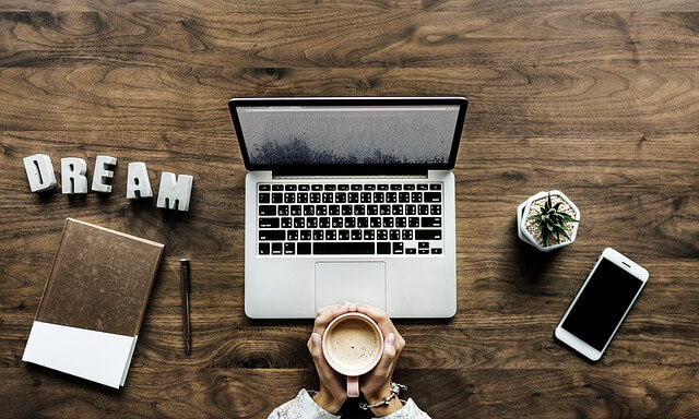 ノートパソコンの前でコーヒーを包む手