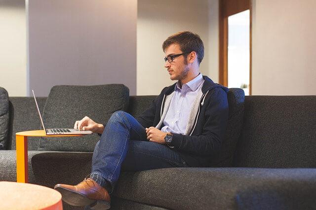 ソファーの上でパソコンを見る外人男性