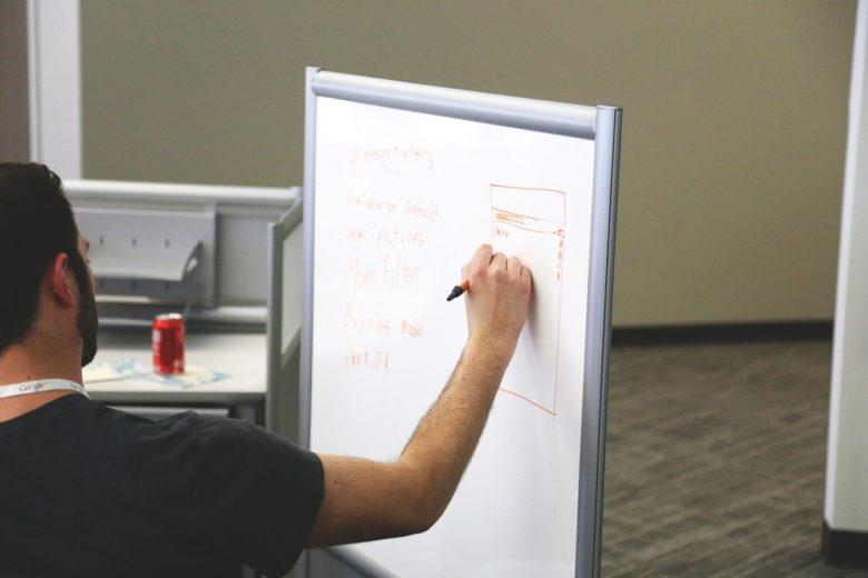 ホワイトボードに書く男性